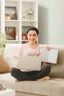 Młoda kobieta siedzi na kanapie za stolikiem kawowym, trzymając i używanego laptopa z książką w salonie
