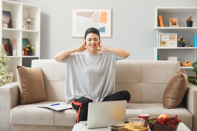Młoda kobieta siedzi na kanapie za stolikiem kawowym w salonie