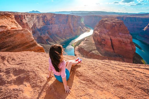 Młoda kobieta siedzi na krawędzi klifu z widokiem na horseshoe bend w page arizona