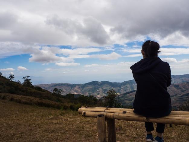 Młoda kobieta siedzi na krześle i zobaczyć niebo, siedzieć sama
