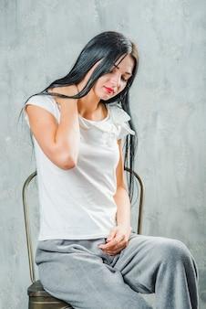 Młoda kobieta siedzi na krześle na szarym tle o ból szyi