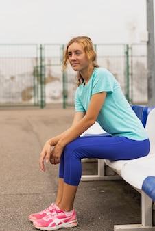 Młoda kobieta siedzi na krześle, patrząc od hotelu