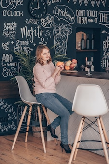 Młoda kobieta siedzi na krześle przy biurku w nowoczesnej kuchni na poddaszu i gra w żonglerki pomarańczami.