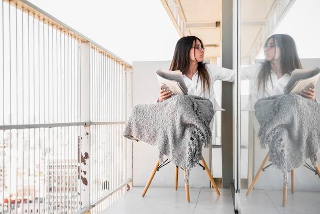 Młoda kobieta siedzi na krześle w balkonie czytanie gazety