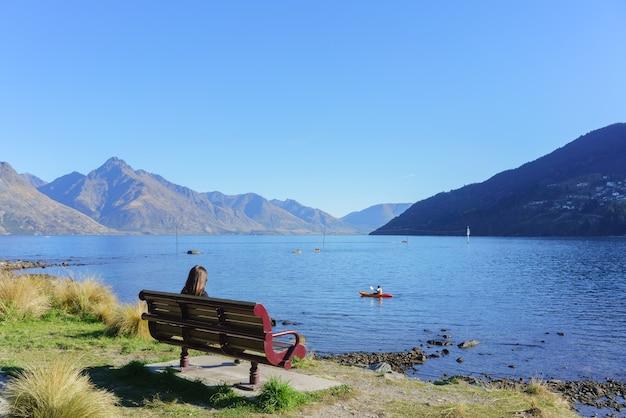 Młoda kobieta siedzi na krześle w queenstown garden, położonym obok miasta queenstown i jeziora wakatipu jesienią, południowa wyspa nowej zelandii