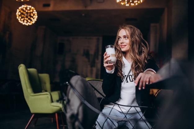 Młoda kobieta siedzi na krześle wewnątrz kawiarni