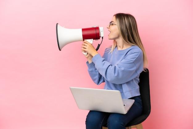 Młoda kobieta siedzi na krześle z laptopem na odosobnionym różowym tle krzycząc przez megafon