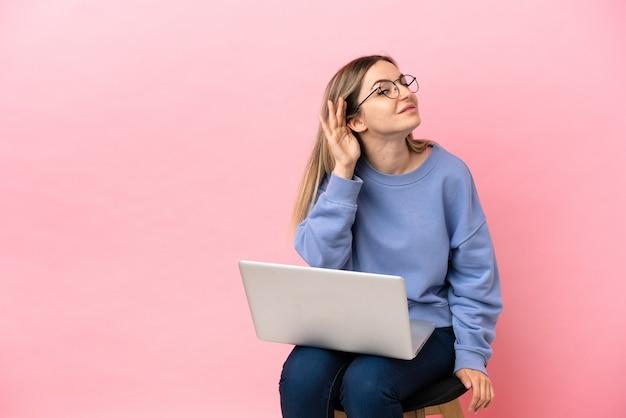 Młoda kobieta siedzi na krześle z laptopem na odosobnionym różowym tle, słuchając czegoś, kładąc rękę na uchu
