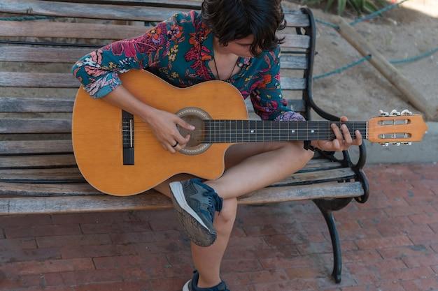 Młoda kobieta siedzi na ławce grając na gitarze w parku.