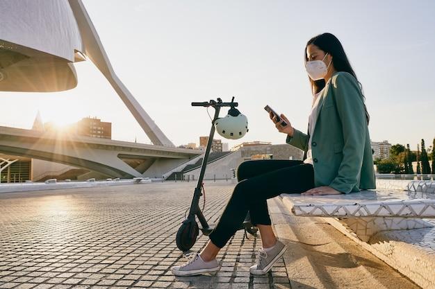 Młoda kobieta siedzi na ławce przy użyciu telefonu komórkowego. kobieta ubrana w maskę podczas korzystania z hulajnogi elektrycznej