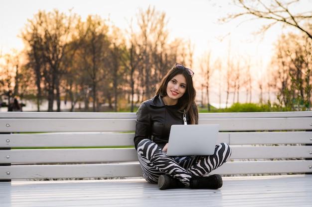 Młoda kobieta siedzi na ławce, w pobliżu uniwersytetu, pracując z laptopem