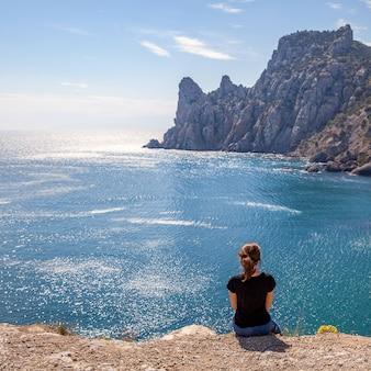 Młoda kobieta siedzi na ławce z widokiem na morze