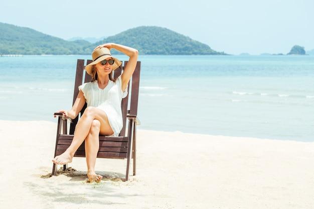 Młoda kobieta siedzi na leżaku na tropikalnej plaży