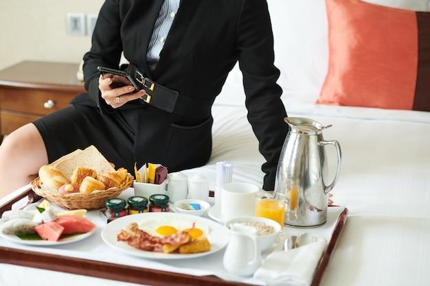 Młoda kobieta siedzi na łóżku hotelowym, je śniadanie i sprawdza media społecznościowe na swoim smartfonie