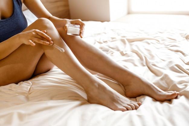 Młoda kobieta siedzi na łóżku w nocy. wytnij widok kremu na nodze. samo pielęgnacja i pielęgnacja skóry. w dłoni trzyma kremowy słoik. światło dzienne.
