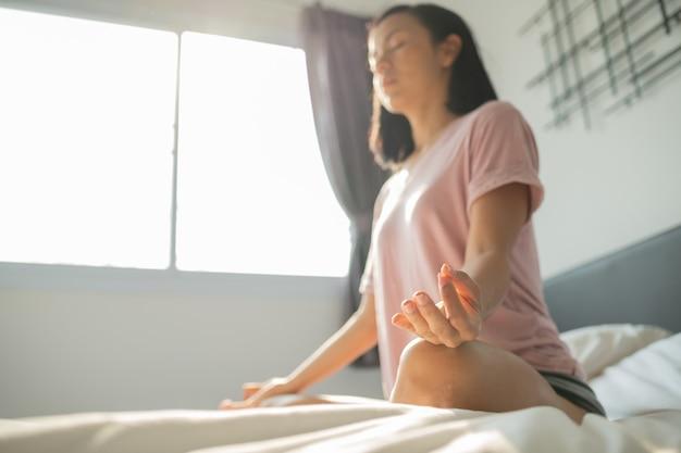 Młoda kobieta siedzi na łóżku w sypialni i medytacji.
