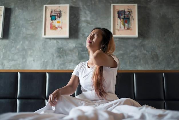 Młoda kobieta siedzi na łóżku z bólem szyi po przebudzeniu