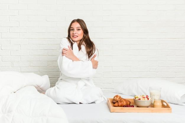 Młoda kobieta siedzi na łóżku