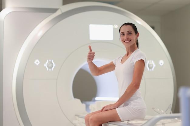 Młoda kobieta siedzi na maszynie do rezonansu magnetycznego i pokazuje kciuk w górę