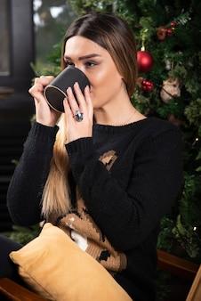 Młoda kobieta siedzi na nowoczesnym fotelu, relaks i picie kawy lub herbaty. wysokiej jakości zdjęcie