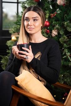 Młoda kobieta siedzi na nowoczesnym krześle i trzyma filiżankę kawy lub herbaty. wysokiej jakości zdjęcie