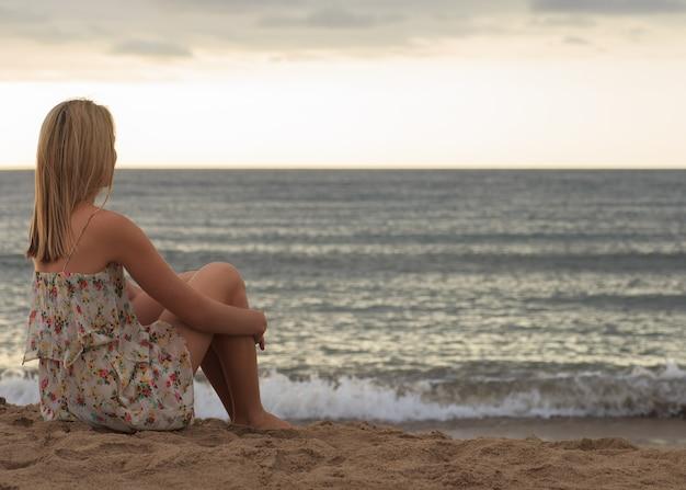 Młoda kobieta siedzi na piasku i patrząc na morze.