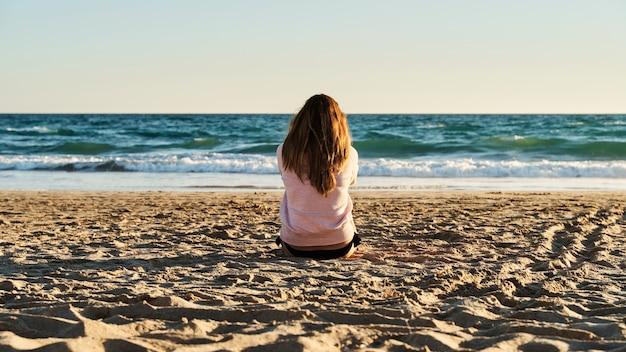 Młoda kobieta siedzi na piasku na plaży, oglądając zachód słońca