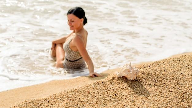 Młoda kobieta siedzi na plaży i patrząc na morskie fale