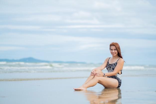 Młoda kobieta siedzi na plaży, podróżuje na wakacje, dziewczyna cieszy się w lecie. zrelaksować się na plaży. szczęśliwy czas, powołanie