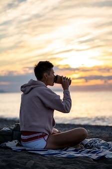 Młoda kobieta siedzi na plaży z filiżanką kawy o wschodzie lub zachodzie słońca