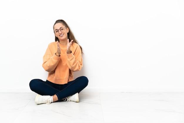 Młoda kobieta siedzi na podłodze brawo po prezentacji na konferencji