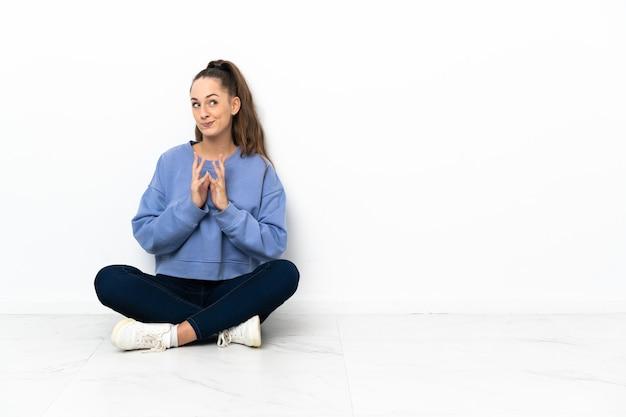 Młoda kobieta siedzi na podłodze coś knuje