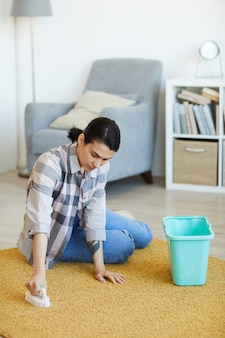 Młoda kobieta siedzi na podłodze i myje dywan środkiem czyszczącym w salonie