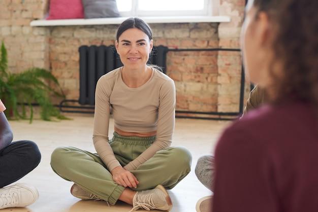 Młoda kobieta siedzi na podłodze i rozmawia z ludźmi podczas zajęć