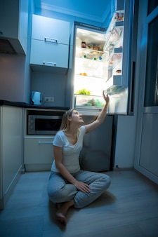 Młoda kobieta siedzi na podłodze i sięga po jedzenie z otwartej lodówki późną nocą