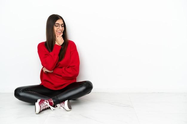 Młoda kobieta siedzi na podłodze na białym tle patrząc w bok