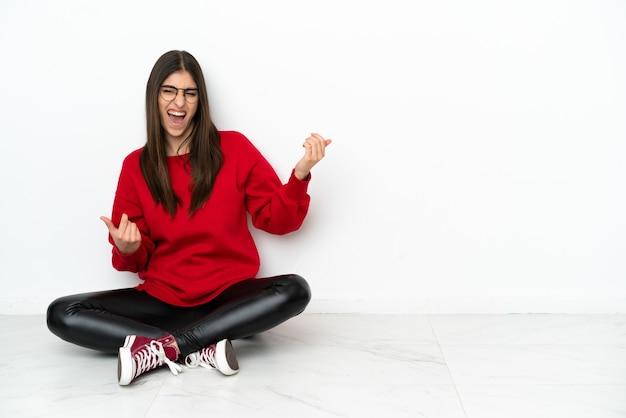 Młoda kobieta siedzi na podłodze na białym tle robiąc gest na gitarze