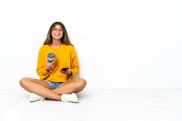 Młoda kobieta siedzi na podłodze na białym tle trzymając kawę na wynos i telefon komórkowy