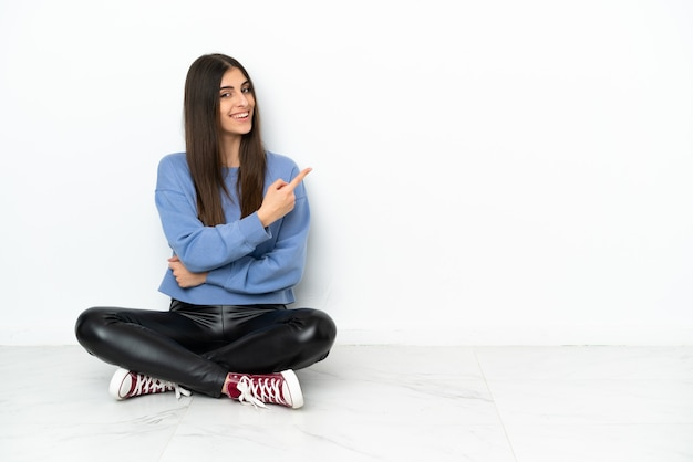 Młoda kobieta siedzi na podłodze na białym tle, wskazując na bok, aby zaprezentować produkt
