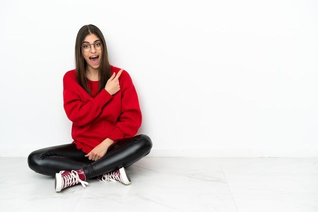 Młoda kobieta siedzi na podłodze na białym tle zaskoczona i wskazująca bok