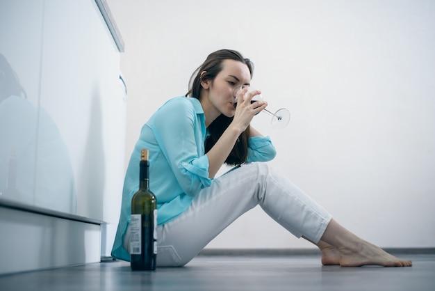 Młoda kobieta siedzi na podłodze, picie wina, alkoholizm, depresja, rozwód