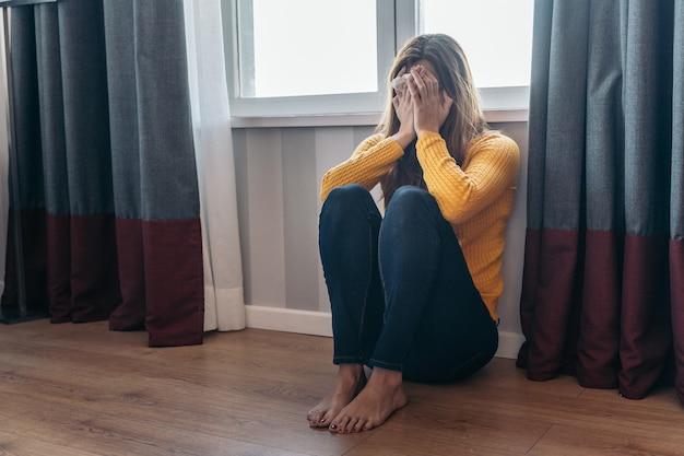 Młoda kobieta siedzi na podłodze po tym, jak została wykorzystana przez swojego partnera. pojęcie przemocy i znęcania się nad kobietami.