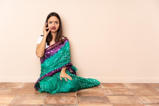Młoda kobieta siedzi na podłodze pokazując znak gestu ciszy