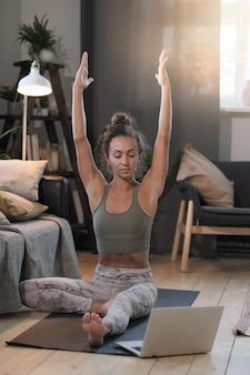 Młoda kobieta siedzi na podłodze przed laptopem i medytuje online w pokoju