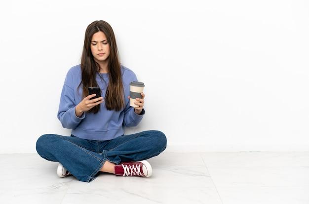 Młoda kobieta siedzi na podłodze trzymając kawę na wynos i telefon komórkowy
