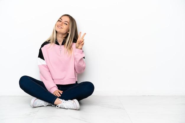 Młoda kobieta siedzi na podłodze w pomieszczeniu, uśmiechając się i pokazując znak zwycięstwa