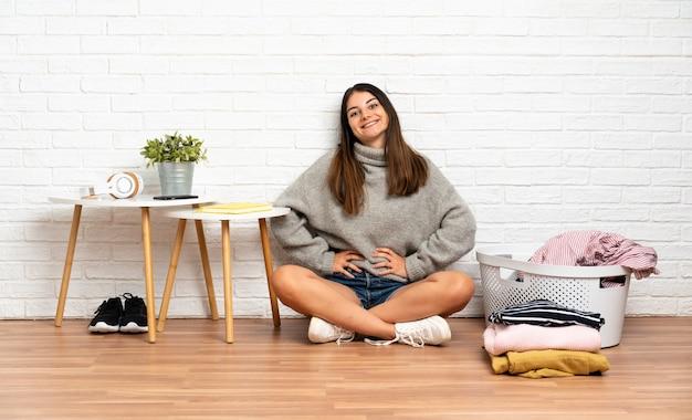 Młoda kobieta siedzi na podłodze w pomieszczeniu z koszem na ubrania pozowanie z rękami na biodrze i uśmiecha się