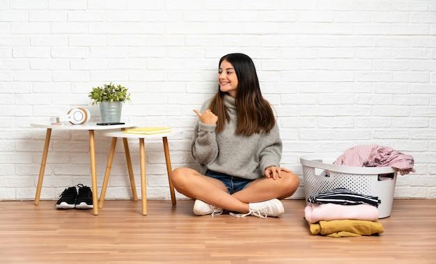 Młoda kobieta siedzi na podłodze w pomieszczeniu z koszem na ubrania skierowanym w bok, aby przedstawić produkt