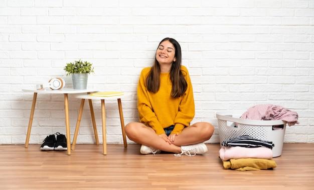 Młoda kobieta siedzi na podłodze w pomieszczeniu z koszem na ubrania śmiejąc się