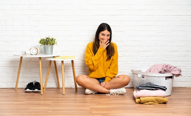 Młoda kobieta siedzi na podłodze w pomieszczeniu z koszem na ubrania szczęśliwa i uśmiechnięta szyszka usta rękami